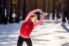 Young woman exercising in the fresh air in the Park. Young sports woman model exercising during winter training outside in cold snow sunny weather in the Park Royalty Free Stock Photo