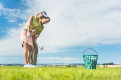 Young woman exercising the golf swing helped by her instructor. Full length side view of a young women holding an iron club, while exercising the golf swing Stock Image