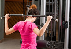 Young woman exercising with gym bar for her back Royalty Free Stock Photography