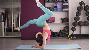 Young woman exercising in gym on a blue mat, doing yoga sequence balance on her hands and stretching.  stock video
