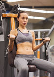 Young woman exercising on gym machine Stock Image