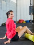 Young Woman Exercising In Gym. Side view portrait of smiling young woman exercising in gym Royalty Free Stock Images