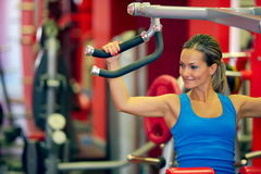Young woman exercising in the gym. Young smiling woman exercising in the gym Royalty Free Stock Photography