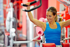 Young woman exercising in the gym. Young smiling woman exercising in the gym Stock Photo