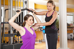 Young woman exercising in gym with trainer. A smiling beautiful young women in her twenties exercising in a fitness studio training her latissimus and being Royalty Free Stock Photos