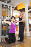 Young woman exercising in gym with trainer. A smiling beautiful young women in her twenties exercising in a fitness studio training her latissimus and being Stock Image