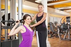 Young woman exercising in gym with trainer. A smiling beautiful young women in her twenties exercising in a fitness studio training her latissimus and being Royalty Free Stock Photo