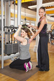 Young woman exercising in gym with trainer. A smiling beautiful young women in her twenties exercising in a fitness studio training her latissimus and being Royalty Free Stock Image
