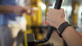Young woman exercising in gym under coach supervision, using fitness bracelet. Stock footage stock footage