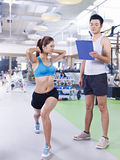 Young woman exercising in gym. Young women working out in gym with partner/trainer Stock Image