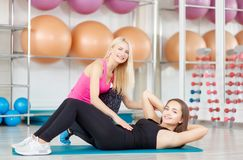 Young woman exercising with her fitness instructor royalty free stock photos