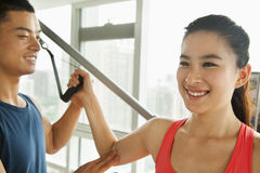 Young woman exercising with his personal trainer in the gym Royalty Free Stock Photos