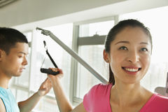 Young woman exercising with his personal trainer in the gym Stock Images