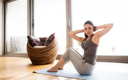 Young woman exercising at home, doing crunches. royalty free stock photo