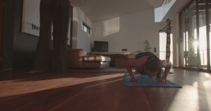 Young woman exercising at home doing push ups stock video