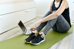 Young woman exercising at home doing yoga and looking at her tablet computer Royalty Free Stock Photos