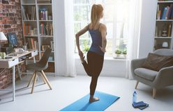 Woman doing stretching exercises at home. Young woman exercising at home in the living room, she is stretching her leg, fitness and wellness concept stock photos