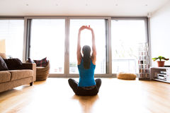 Young woman exercising at home, stretching arms. Royalty Free Stock Image