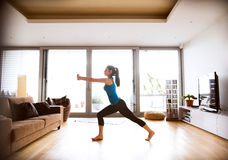 Young woman exercising at home, stretching legs and arms. Stock Photo