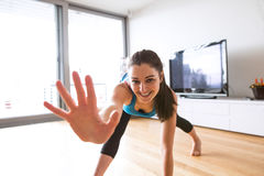 Young woman exercising at home, stretching legs and arms. Royalty Free Stock Photography