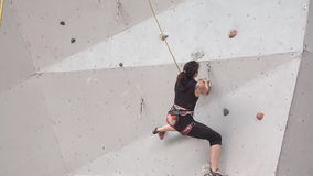 Young woman exercising at indoor climbing gym wall. slow motion. training climbers on the climbing wall. girl has