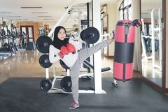 Young woman exercising a kick with boxing sack. Young woman wearing sportswear and veil while exercising a kick with boxing sack in the gym center Stock Image