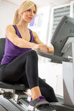 Young woman exercising on a machine Royalty Free Stock Images