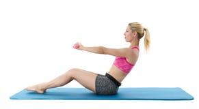 Young woman exercising on mat Stock Photo