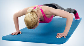 Young woman exercising on mat Royalty Free Stock Images