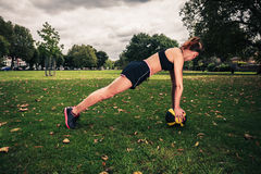 Young woman exercising with medicine ball in park Stock Photos
