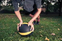 Young woman exercising with medicine ball in park Stock Photo