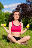Young woman exercising in nature. Young woman exercising with dumbbells in nature Stock Images