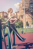 Young woman exercising outdoors. Woman in outdoor gym Stock Photography