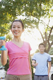 Young Woman Exercising in Park with Dumbells Stock Images