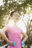 Young Woman Exercising in Park with Dumbells Stock Photo