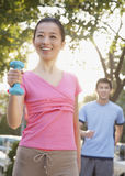 Young Woman Exercising in Park with Dumbells Stock Photography