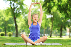 Young woman exercising in a park. On a sunny day Stock Image