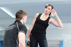 Young woman exercising with personal trainer Stock Image