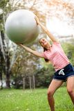 Young woman exercising with pilates ball in the park. Yoga instructor holding fitness ball over her head and training. Active sport lifestyle in urban royalty free stock images