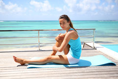 Young woman exercising by pool and beach Royalty Free Stock Images