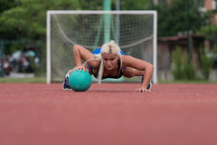 Young Woman Exercising Push-Ups On Medicine Ball Outdoor Stock Photography
