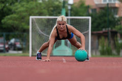 Young Woman Exercising Push-Ups On Medicine Ball Outdoor Stock Photo