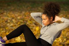 Young woman exercising sit ups outdoors Royalty Free Stock Photos