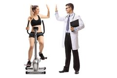 Young woman exercising on a stationary bike and high-fiving a do. Young women exercising on a stationary bike and high-fiving a doctor isolated on white Stock Image