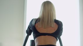 Young woman exercising on a stepper apprentice, back view stock footage
