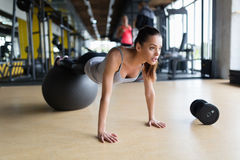 Young woman exercising with swiss ball in gym royalty free stock images