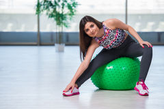 The young woman exercising with swiss ball in health concept Royalty Free Stock Image