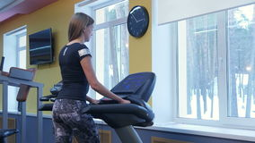 Young woman exercising on treadmill in the gym stock video footage