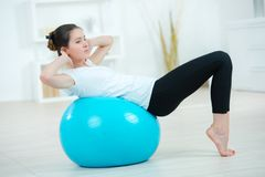 Young woman exercising using gym ball Royalty Free Stock Images