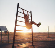Young woman exercising on wall bars with her legs up Royalty Free Stock Photos